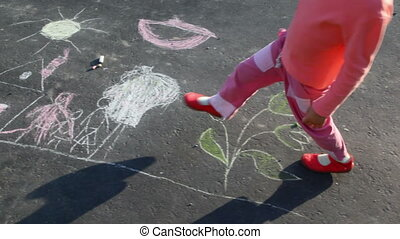 little girl walking on drawing on asphalt