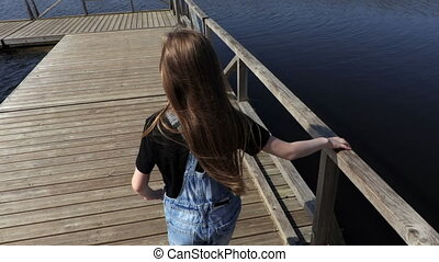 Little girl walking on floating bridge in lake