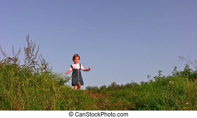 little girl walking on meadow alone