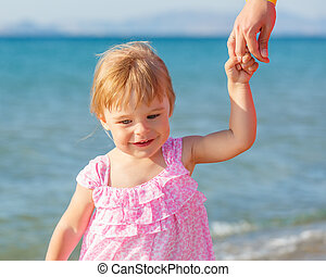 Little girl walking on the beach