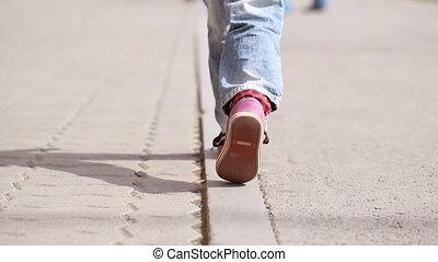 Little girl walking on the sidewalk