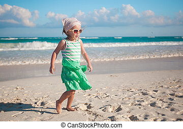 Little girl walking on white sandy beach in Mexico