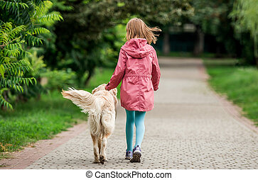 Little girl walking with dog in park