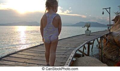 Little Girl Walks along Wooden bridge on Beach at Sunset