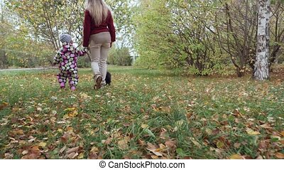 Little girl walks and plays with spitz dog in the autumn park.