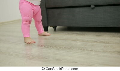little girl walks barefoot in her living room,