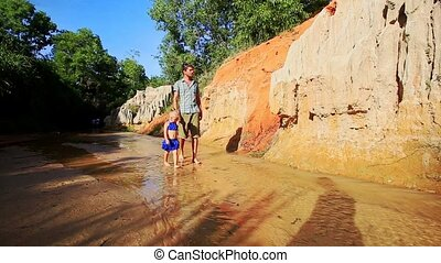 Little Girl Walks by Hand with Dad on Fairy Stream