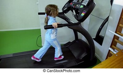 Little girl walks by treadmill and looks to panel with hands...