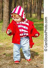 Little girl walks  in a wood