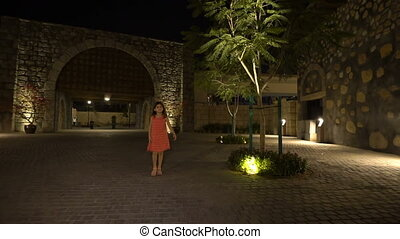 Little girl walks in the ancient city at night, slow motion