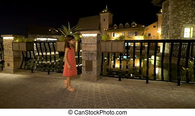Little girl walks in the ancient city at night 2 - Little...