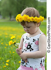 little girl walks on a glade with dandelions