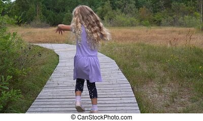 Little girl walks on a hiking trail in a park or forest. Little brave girl in violet dress walking alone on wooden path. Hiking and walking in nature. Camera movement follow shot with gimbal.