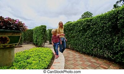 Little Girl Walks on Flowerbed in Hedge Labyrinth Mother Looks