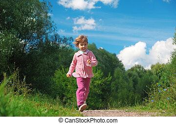 little girl walks on path outdoor in summer