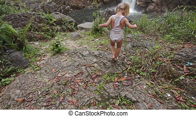 Little Girl Walks on Stone Surface against High Waterfall...