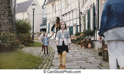 Little girl walks to camera, relaxed and smiling. European mother together with two kids. Half timber houses Germany 4K.