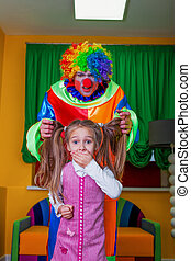 Little girl was frightened of the clown. - Little girl was...