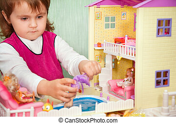 little girl washes a doll in pool of toy house