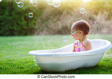 little girl washes in the bathroom on the green grass
