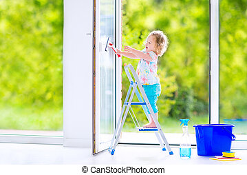 Little girl washing a window - Cute laughing curly toddler...