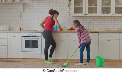 Little girl washing floor with mop in kitchen - Positive ...