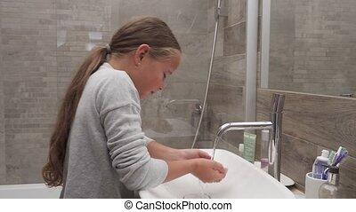 Little girl washing her face in bathroom - Cute little girl...