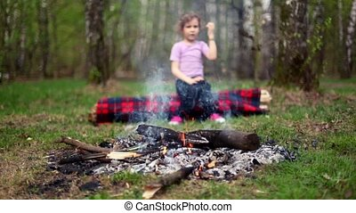 Little girl watch at bonfire burn, boy come and sit near