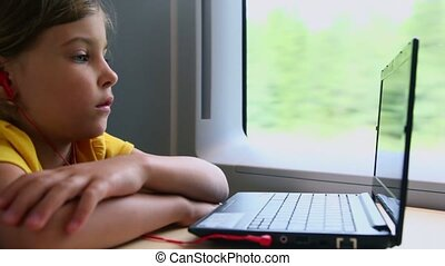 Little girl watch on notebook when sits at train near window