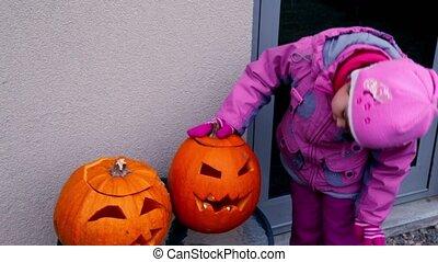 Little girl watch on two halloween pumpkin heads