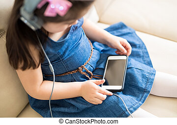 Little girl watching cartoon movie on cell phone