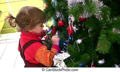 little girl watching christmas tree in shop - Little girl...