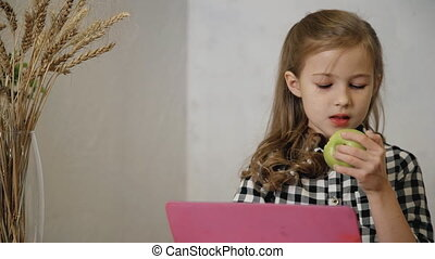 Little girl watching educational video on tablet computer....