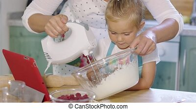 Little girl watching her mother whisk cream