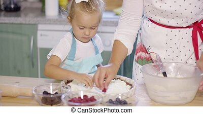 Little girl watching the baking with anticipation - Little...