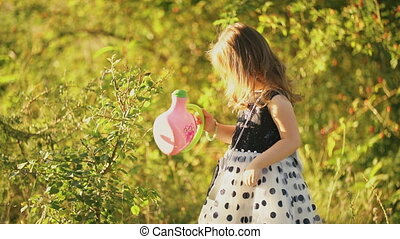 little girl watering a tree on a background of green foliage