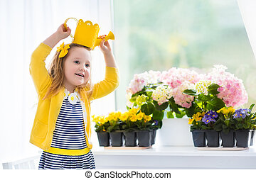 Little girl watering blooming flowers at home - Cute girl...