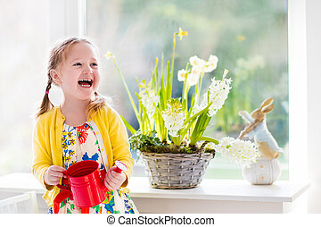 Little girl watering Easter flowers - Cute girl watering...