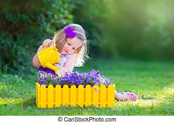 Little girl watering farden flowers - Child working in the...
