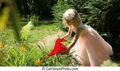 Little girl watering flowers in a garden from a watering can
