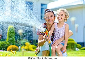 Little girl watering flowers - Portrait of little gardener ...
