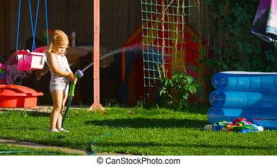 Little girl watering lawn