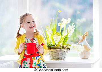 Little girl watering spring flowers - Cute girl watering...