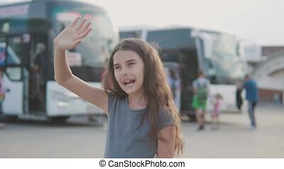 little girl waving her hand at the bus station slow motion...