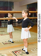 little girl wear pointe in ballet class near frame and large...