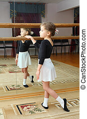 little girl wear pointe trains in ballet class near frame...