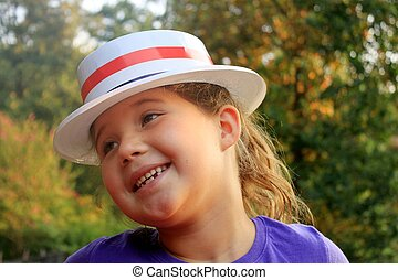 Little girl wearing 4th of July hat and smiling