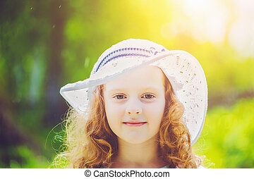 Little girl wearing a hat for protection from sunstroke.