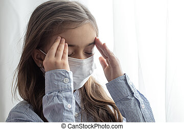 Little girl wearing a protective medical mask from coronavirus close up.
