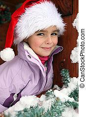 Little girl wearing a Santa hat in a chalet